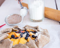 De kokende koekjes met perzik en bosbes, gieten suiker Stock Foto's