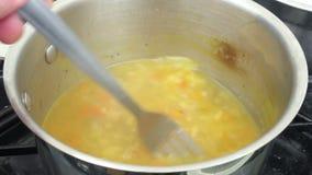De kokende pan van soep op de haardplaat die stired zijn stock videobeelden