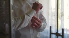 De kokers van bruidegomgrepen op een overhemd thuis stock videobeelden