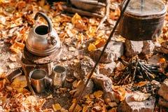 De koks van het diner in een grote pot over een open brand Herfst bos Royalty-vrije Stock Foto