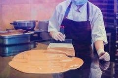 De kokvrouw mengt chocoladeroom met professionele chocoladespatel stock afbeeldingen
