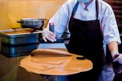 De kokvrouw mengt chocoladeroom met professionele chocoladespatel royalty-vrije stock afbeelding