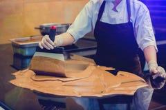 De kokvrouw mengt chocoladeroom met professionele chocoladespatel stock foto