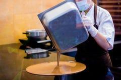 De kokvrouw mengt chocoladeroom met professionele spatel in de chocoladewinkel elted donkere chocolade stock fotografie