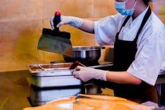 De kokvrouw mengt chocoladeroom met professionele spatel in de chocoladewinkel elted donkere chocolade royalty-vrije stock afbeeldingen
