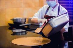 De kokvrouw mengt chocoladeroom met professionele spatel in de chocoladewinkel elted donkere chocolade stock afbeelding