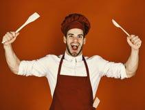 De kokwerken in keuken De chef-kok met opgewekt gezicht houdt houten lepel en spatel op rode achtergrond Keukengerei en het koken stock afbeelding