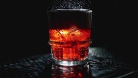 De kola giet in een glas met ijsblokjes Sluit omhoog Langzame motie 100fps stock videobeelden