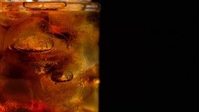 De kola met ijs en de bellen in glas roteren op zwarte stock footage