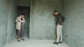 De kolonisten inspecteren de ruimte in een ruwe afwerking bouw, huis het kopen stock footage