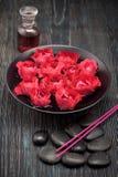 De kom met bloemenrozen, zwarte stenen en nam olie toe Royalty-vrije Stock Fotografie