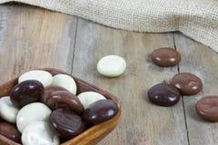 De kom met chocolade wordt gevuld kruidnoten op houten oppervlakte die Royalty-vrije Stock Foto's
