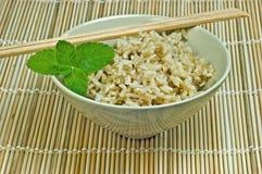 De kom van de rijst op bamboemat met eetstokjes Stock Afbeeldingen