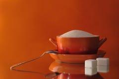 De kom van de suiker met een theelepeltje op een oranje achtergrond Stock Afbeeldingen
