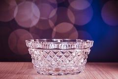 De kom van het kristalglas met bokehachtergrond Stock Foto's