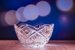 De kom van het kristalglas met bokehachtergrond Stock Afbeeldingen