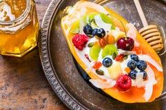 De kom van het ontbijtfruit met vruchten, bessen en noten stock foto's