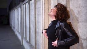 De komische kerel gekleed als vrouw, die zwarte kleren en pruik draagt, zingt buiten stock video