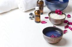 De kommen met schoonheidsmiddelenproducten, handdoeken, flessen met olie op witte oppervlakte, bieden ruimte het hoofd Concept ku stock foto