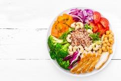 De komschotel van Boedha met kippenfilet, ongepelde rijst, peper, tomaat, broccoli, ui, kikkererwt, verse slasalade, cachou en wa stock foto