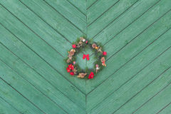 De Komstkroon van Kerstmisholyday het hangen buiten bij groene houten deurachtergrond Stock Foto's