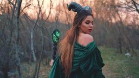 De koningin van de andere wereldlood in kloof, meisje met grote zwarte hoornen op haar hoofd is gekleed in lang, groen verbazen stock video