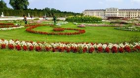 De Koninklijke tuinen van het Scönbrunnpaleis met arbeiders die het gazon maaien stock afbeelding