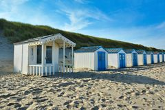 White and blue beach huts on island Texel in the Netherlands with blue sky on sunny day