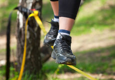De koorddanser is op een strakke slinger, die op de bomen, bij een lage hoogte wordt bevestigd stock afbeelding