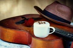 De kop, de gitaar en de hoed van de cappuccinokoffie royalty-vrije stock afbeelding