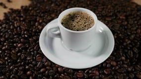 De kop en coffe de bonen van Coffe Een witte kop van verdampende koffie op de lijst met geroosterde boon stock videobeelden