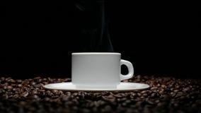 De kop en coffe de bonen van Coffe Een witte kop van verdampende koffie op de lijst met geroosterde boon Een kop met coffeboon zo stock footage