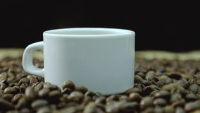 De kop en coffe de bonen van Coffe Een witte kop van verdampende koffie op de lijst met geroosterde boon 4K stock videobeelden
