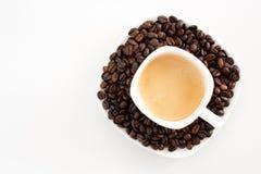 De kop en de bonen van de koffie op een witte achtergrond Stock Afbeeldingen