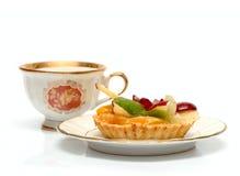 De kop en de cake van de thee in plaat die op wit wordt geïsoleerde royalty-vrije stock foto's