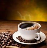 De kop en de schotel van de koffie op een houten lijst. Royalty-vrije Stock Afbeeldingen