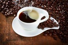 De kop en de schotel van de koffie op een houten lijst Schuim in de vorm van het hart Royalty-vrije Stock Afbeeldingen