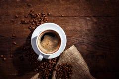 De kop en de schotel van de koffie op een houten lijst Schuim in de vorm van het hart Stock Foto