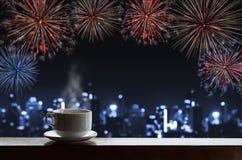 De kop hete dranken op houten bureau met nieuw jaar viert vuurwerk, het blauwe licht van defocusbokeh van gebouwen in de stad stock foto's
