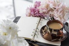 De kop, koffie met suikergoed op de agenda dichtbij het venster, hydrangea hortensia bloeit stock afbeeldingen