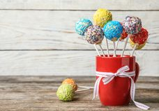 De kop met boog en yummy kleurrijke cake knalt op lijst stock afbeelding