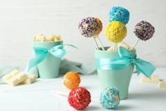 De kop met boog en yummy kleurrijke cake knalt op lijst stock foto