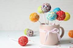 De kop met boog en yummy kleurrijke cake knalt op lijst royalty-vrije stock fotografie