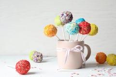 De kop met boog en yummy kleurrijke cake knalt Ruimte voor tekst stock foto