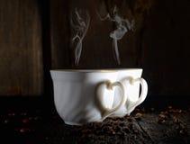 De kop met geurige koffie, geroosterde koffiebonen op een donkere houten achtergrond Stock Foto