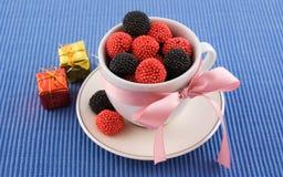 De kop met suikergoed en roze boog Stock Foto's