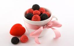 De kop met suikergoed, roze boog en rood hart Stock Foto's
