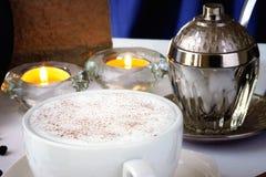 De kop van de cappuccinokoffie, koffiebonen en kaarsen stock fotografie