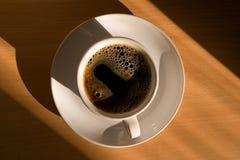 De kop van de koffie in de ochtendzon Stock Foto