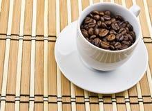De kop van de koffie die met koffiebonen wordt gevuld Stock Afbeelding